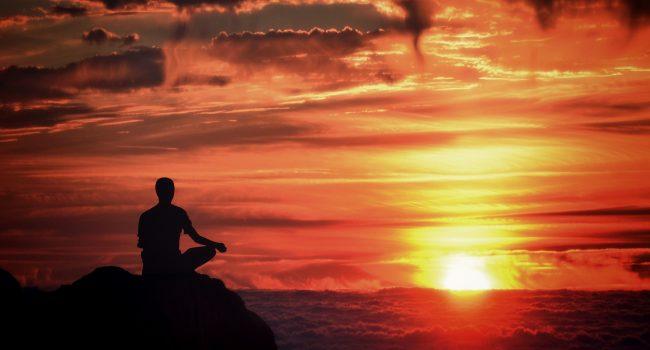 Meditation - Mindfulness - Person Meditating at Sunset Over the